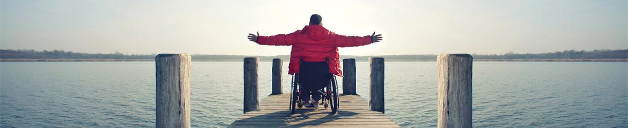 Foto von einem Mann am Steg, der die Arme seitlich ausbreitet. Der Mann sitzt in einem Rollstuhl.