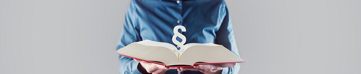 Bild vom Oberkörper eines Mannes. Er hält ein Buch in der Hand. Darüber ist ein Paragraphen-Symbol zu sehen.