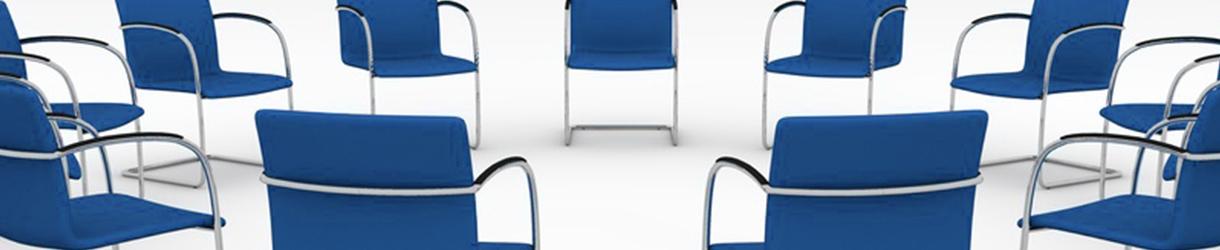Bild von vielen Stühlen, die im Kreis stehen.