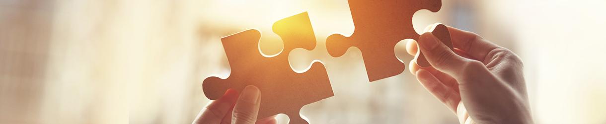 Foto von zwei Händen, die zwei Puzzlestücke zusammenfügen