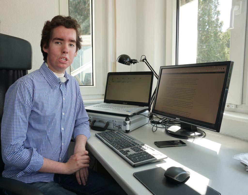Hugo Schmidt sitzt aufrecht an einem Schreibtisch mit zwei Monitoren, einer Tastatur und einer Maus. Er Trägt ein blau-kariertes Hemd und blickt ernst in die Kamera.