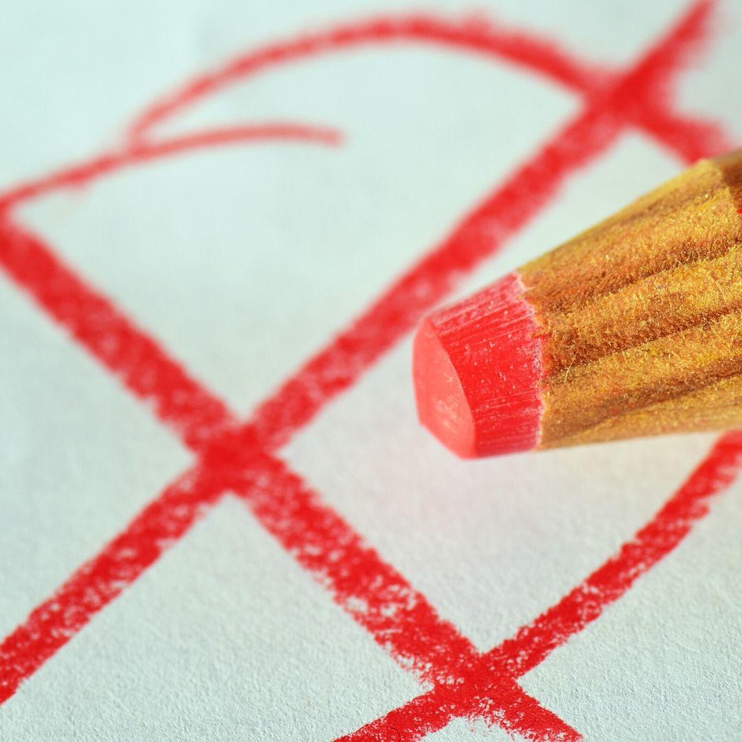 Die Spitze eines roten Buntstifts, darunter ein roter Kreis mit einem roten Kreuz.
