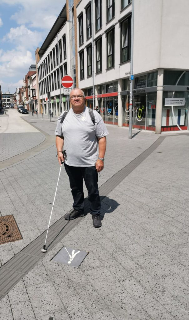 Caus Meier steht in der Innenstadt, er trägt ein hellgraues Tshirt, einen Rucksack und einen Langstock.