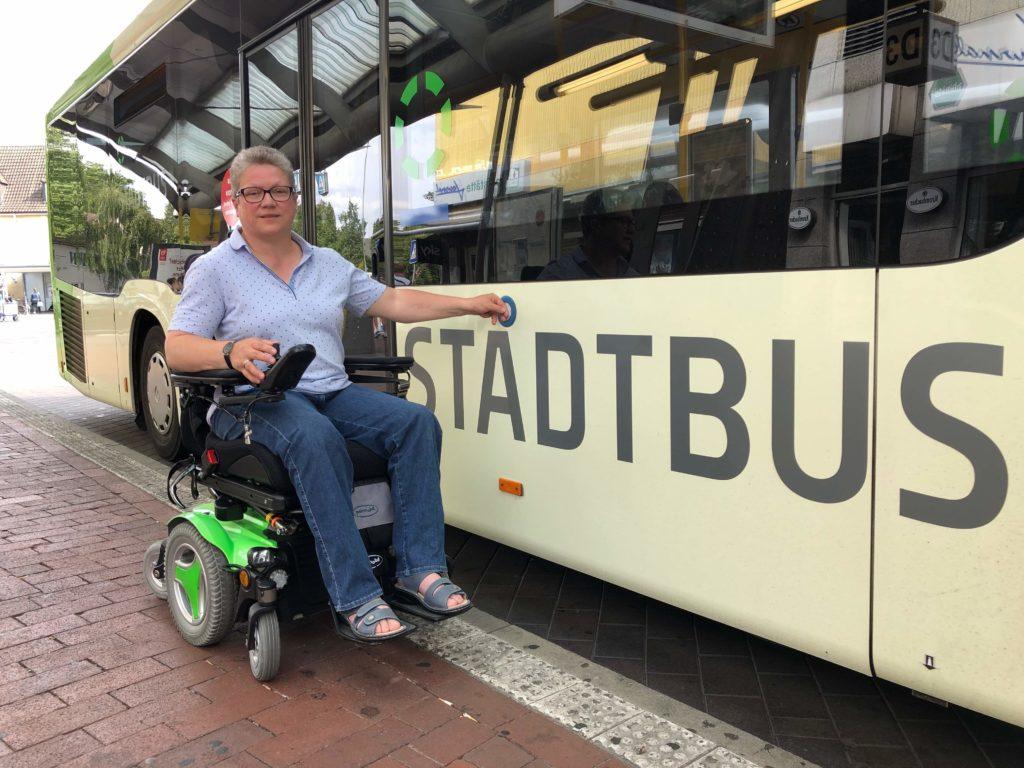 Frau Runte sitzt in ihrem Rollstuhl neben einem Stadtbus und drückt gerade auf den Knopf, der die Türen öffnet.