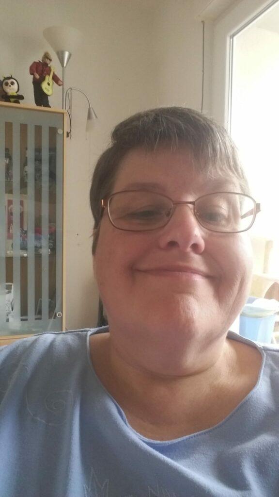 Anke Wortmann blickt in die Kamera und lächelt.