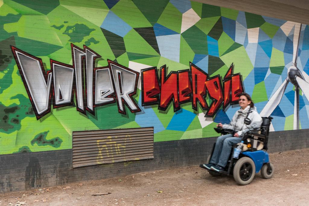 Silke Katzfuß fährt draußen in ihrem Rollstuhl durch. An der Wand befindet sich ein Graffitti. Es steht dort: Voller Energie.