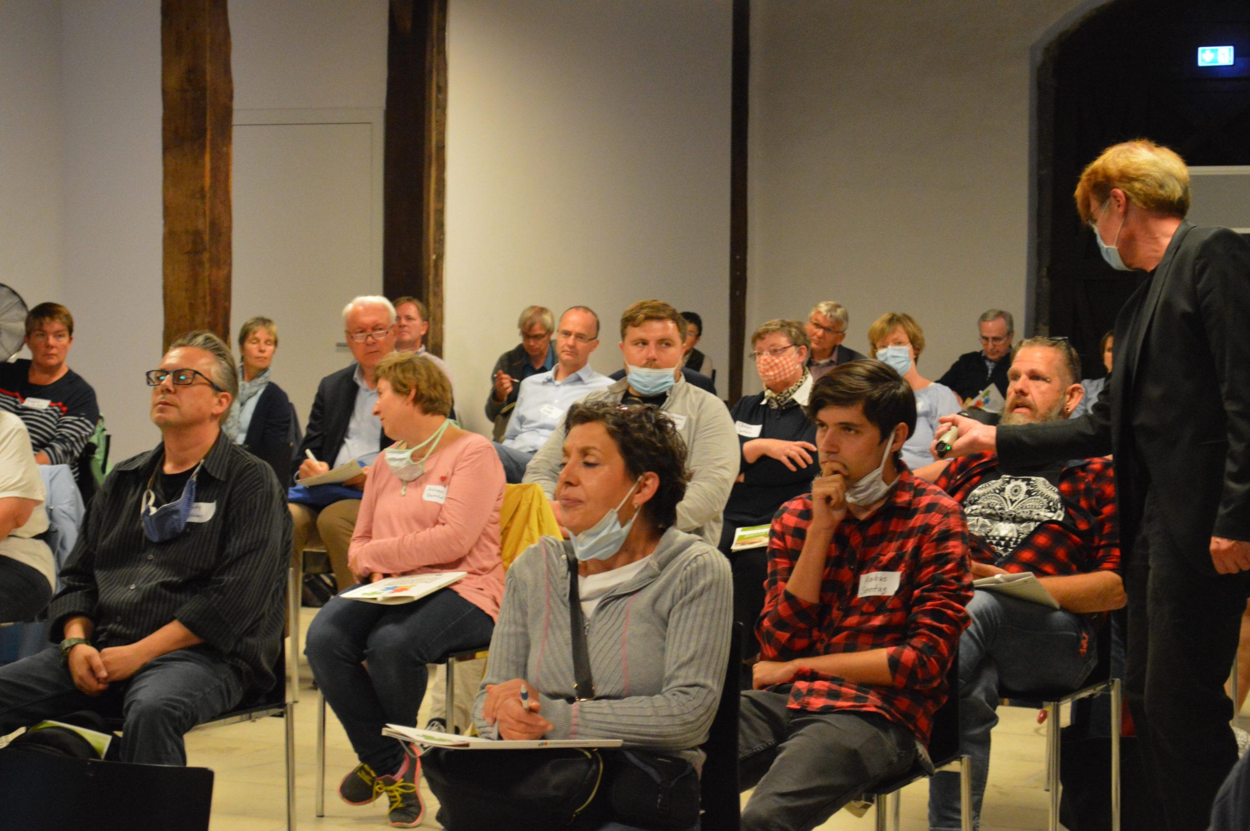 Blick in die Menge: Viele Interessierte sitzen mit Abstand und schauen in Richtung Bühne. Ein Mitarbeiter des Kreises hält einem der Teilnehmer ein Mikrofon hin, damit alle seine Wortmeldung verstehen können..