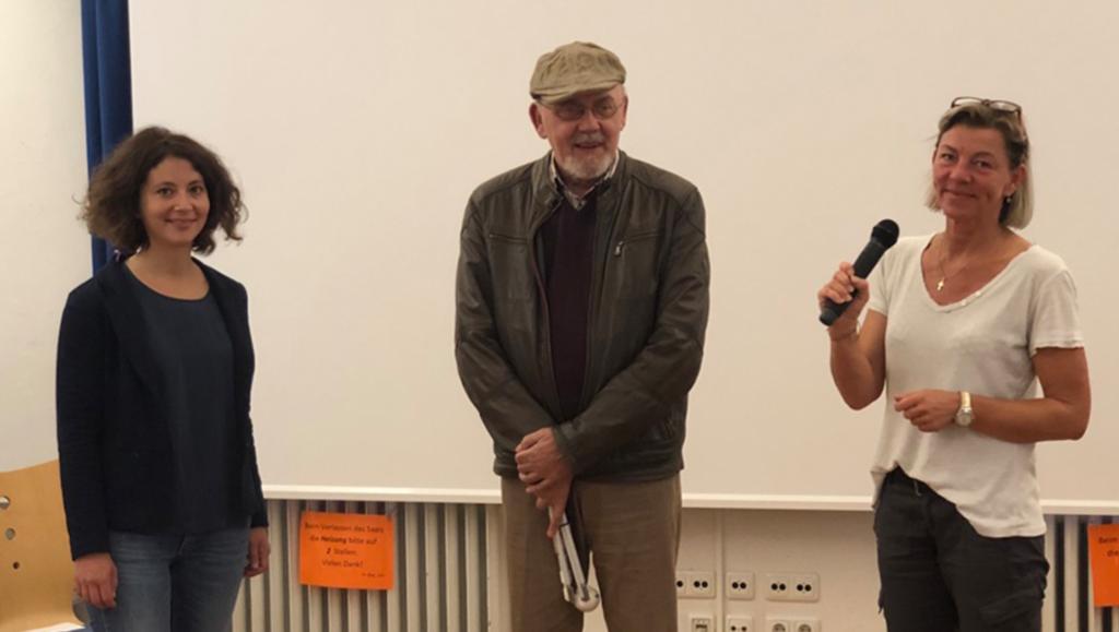 """Die Leiterin des Projekts """"Politische Partizipation Passgenau!"""", Merle Schmidt, gemeinsam mit dem Vorsitzenden des Herforder Beirats für Menschen mit Behinderung, Hans-GerdAdolphy, und Beriatsmitglied ClaudiaRaukohl lächeln in die Kamera. Frau Raukohl hält ein Mikrofon in der Hand."""