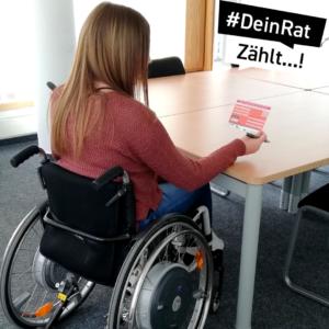 Eine junge Frau im Rollstuhl sitzt an einem Tisch und füllt die Postkarte aus.