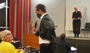 Referent Marcus Windisch steht im Publikum und spricht dabei zu einer Teilnehmerin ins Mikrofon. Im Hintergrund steht Natascha Schlenstedt auf der Bühne. Sie lächelt.
