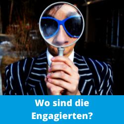 Ein Mann in einem gestreiften Jacket und einer großen blauen, auffälligen Sonnenbrillde hält eine große Lupe vor sein Gesicht. Seine Augen und seine Nase sind stark vergrößert. Es sieht etwas skurril bis witzig aus. Unten ist ein blauer Balken auf dem in Weiß steht: Wo sind die Engagierten?