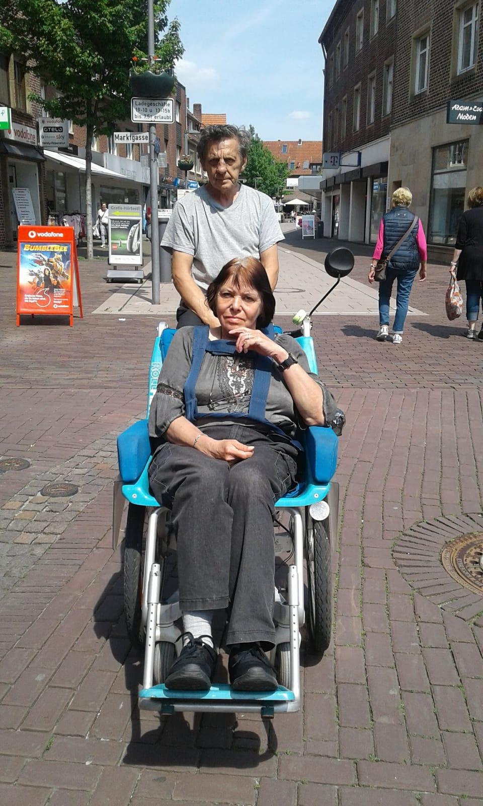 Foto von Herr und Frau König mit ihrem besonderen Tandem Fahrrad. Frau König sitzt vorne in einem Sitz. Herr König fährt das Rad.