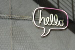 """Eine graue Fassade an der ein Lichtbild in Form einer Sprechblase hängt. In ihr steht """"Hello""""."""