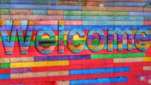 """Eine Fassade aus bunten Holzleisten in blau-, grün-, rot- und lila-Tönen. In der Mitte ragt das Wort """"Welcome"""" aus den Balken hervor."""