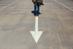 Blick auf eine Straße mit grauem Asphalt, oben im Bild sind die Beine einer Person von hinten zu sehen. Von den Beinen geht ein weißer Pfeil die Richtung des Betrachters ab.