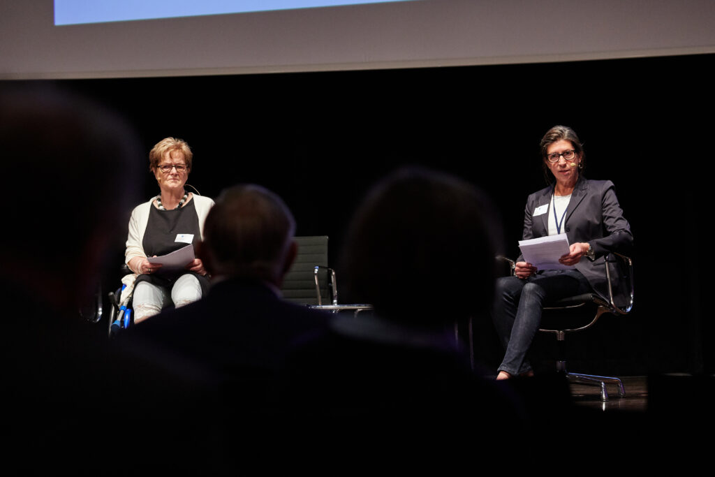Die Vorsitzende Brigitte Piepenbreier sitzt auf einer Bühne. Rechts neben ihr sitzt Melanie Ahlke, die LAG-Geschäftsführerin. Sie hält ein Papier vor sich und spricht gerade zum Publikum.