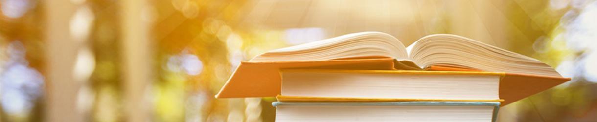 Auf dem Bild wird ein offenes Buch, welches auf anderen Büchern liegt gezeigt.