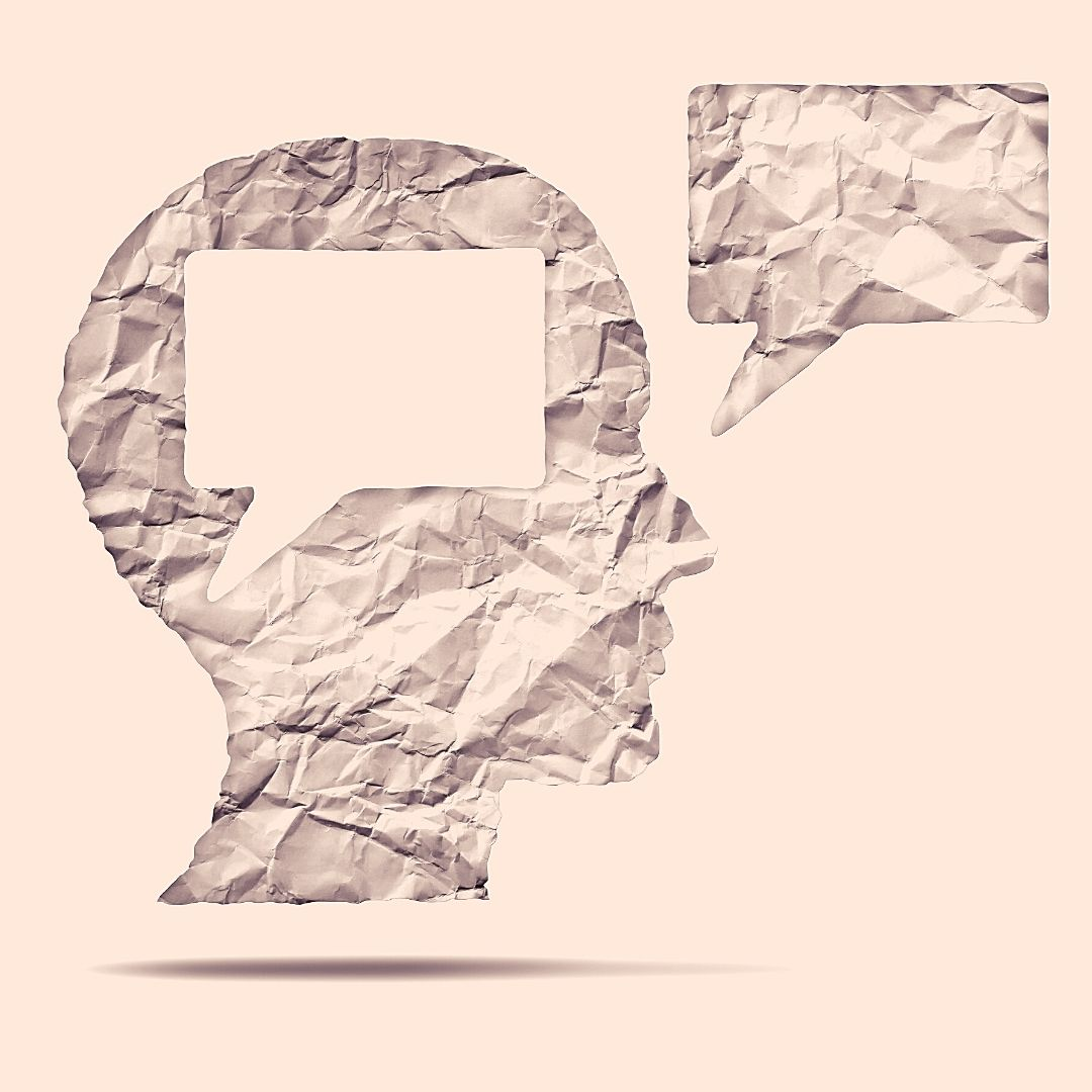 Eine silhouette von einem Kopf aus Papier. Im Kopf wurde eine Sprechblasenform ausgeschnitten, die nun als Sprechblase vor dem Kopf erscheint.