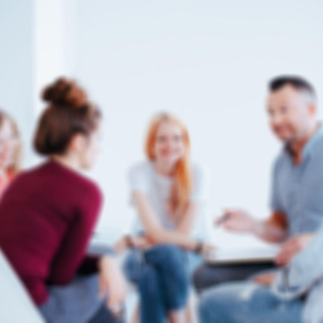 Ein verschwommenes Bild einer Gruppe von menschen, die im Kreis sitzen und miteinander sprechen.