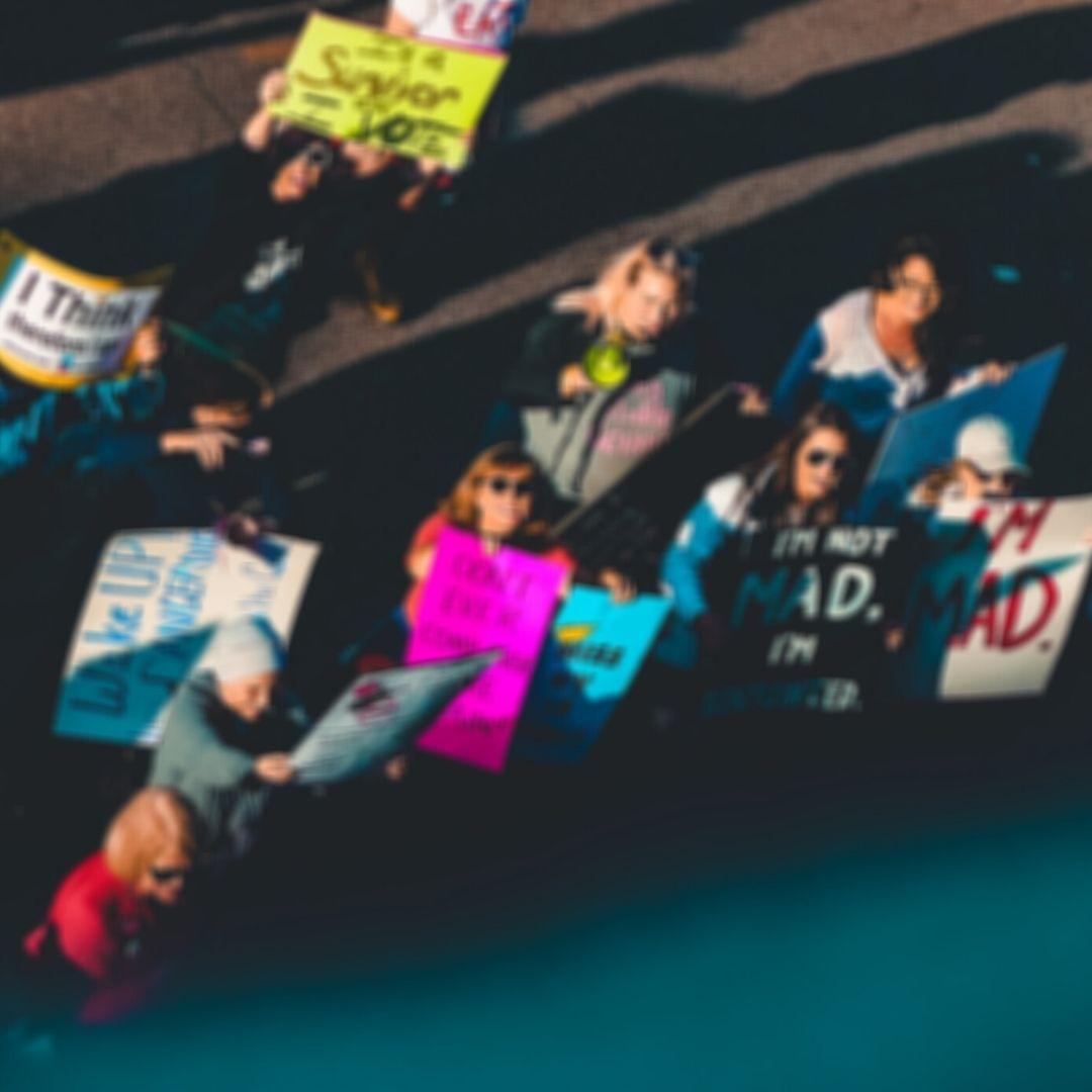 Ein verschwommenes Bild von Demonstrantinnen, die bunte beschriftete Schilder nach oben in die Kamera halten.