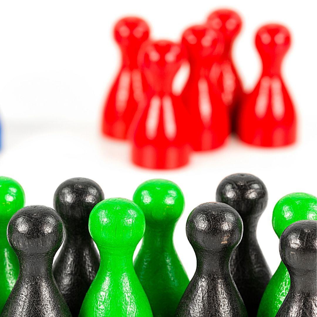 Kleine Spielfiguren stehen nach Gruppen in rot sowie in grün und schwarz