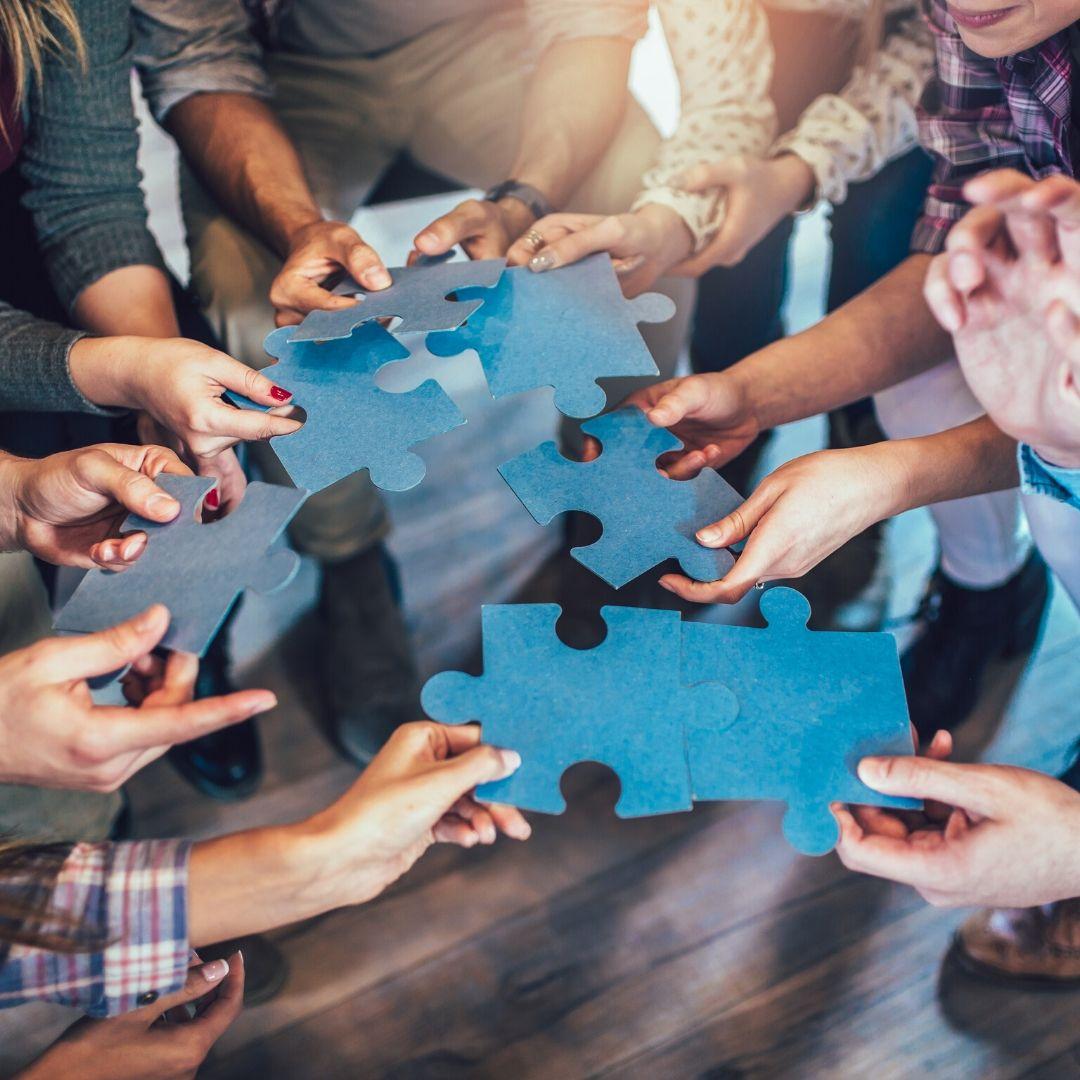 Viele verschiedene Menschen stehen im Kreis und halten große Puzzleteile in die Mitte. Es scheint, als versuchten sie, die passenden Teile zueinanderzubringen.