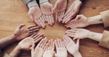 Es sind mehrere Hände, die einen Kreis bilden, zu sehen.