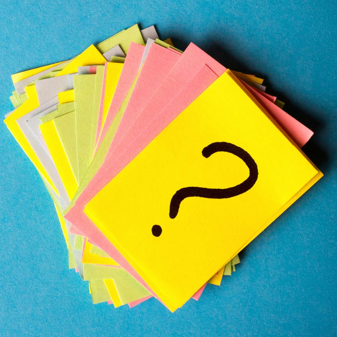 Ein Stapel bunter Zettel, auf dem obersten ist ein schwarzes Fragezeichen gemalt.