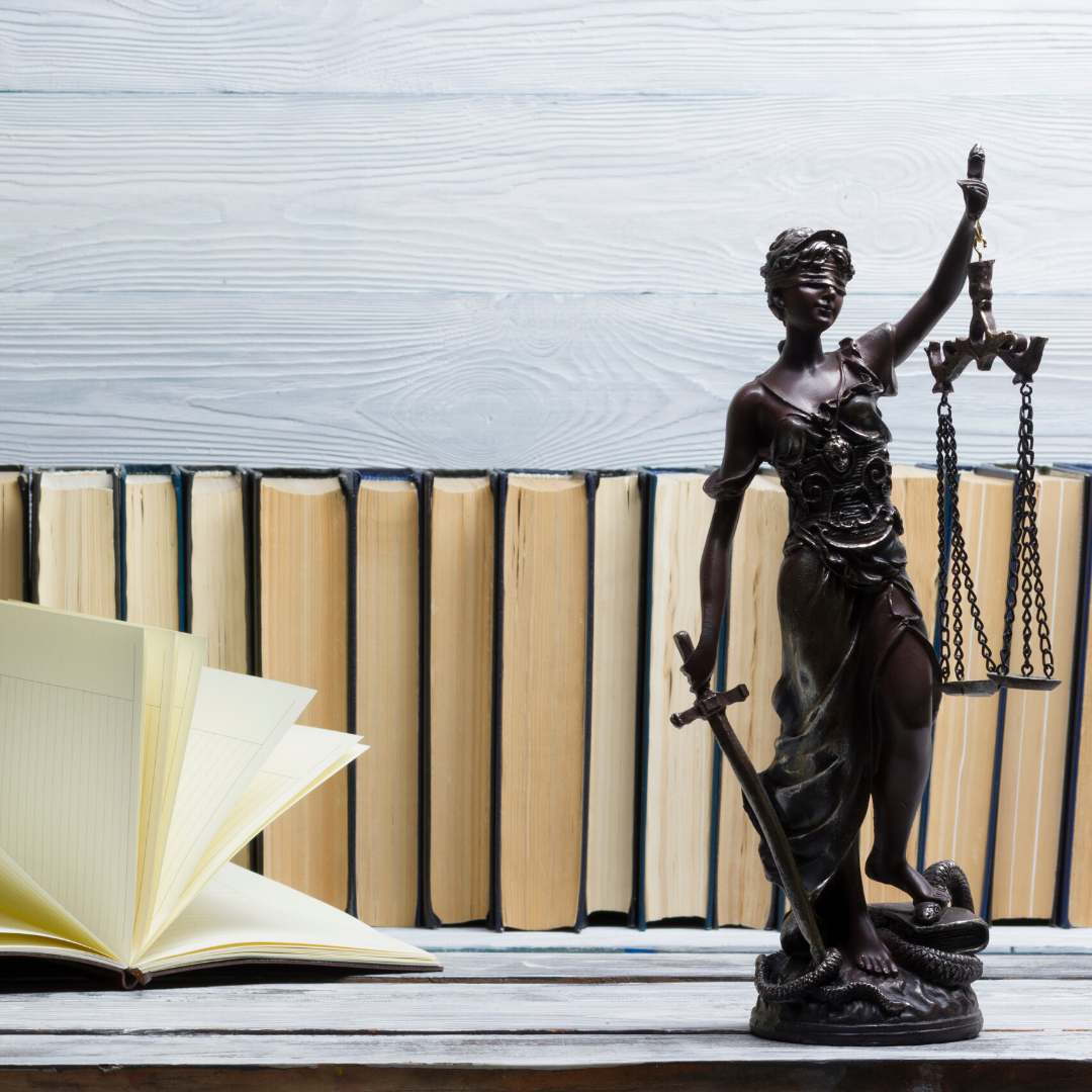 Im Hintergrund eine Buchreihe, links ein aufgeschlagenes Buch, rechts eine kleine bronzene Justiziastatue