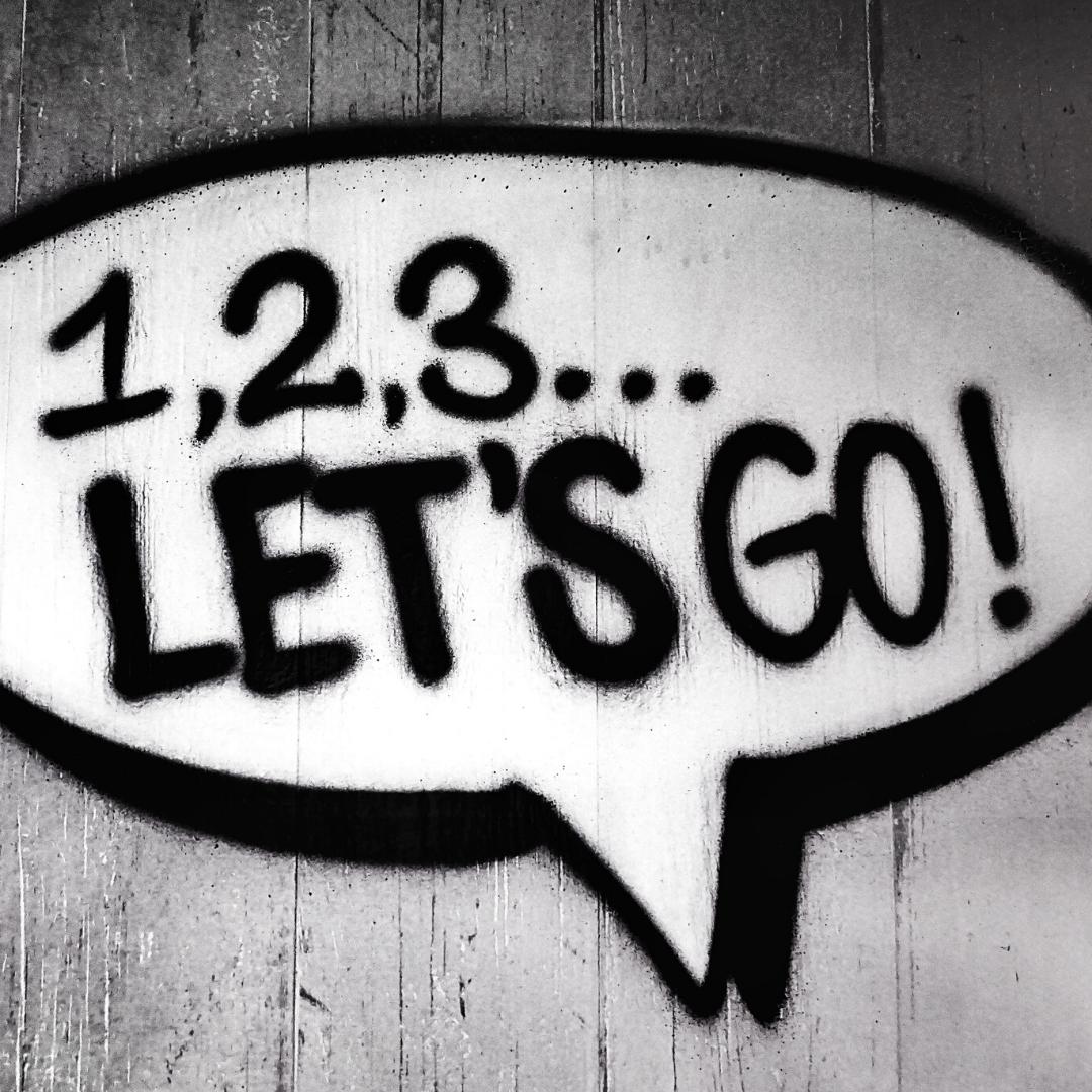 Eine auf eine Wand gesprühte Sprechblase in der steht: 1,2,3...Let's go!
