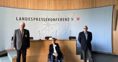 Franz Schrewe, Brigitte Piepenbreier und Horst Vöge blicken direkt in die Kamera. Hinter ihnen befindet sich ein großes Pult und eine helle Wand auf der steht: Landespressekonferenz NRW