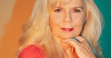 Hildegard Mang blickt leicht eitlich in die Kamera. Ein Handrücken liegt leicht an ihrem Kinn, die andere Hand umgreift das Handgelenk. Das Bild ist sehr farbenfroh und warm. Sie trägt ein korallfarbenes Shirt, der Hintergrund ist teils orange, teils grün.