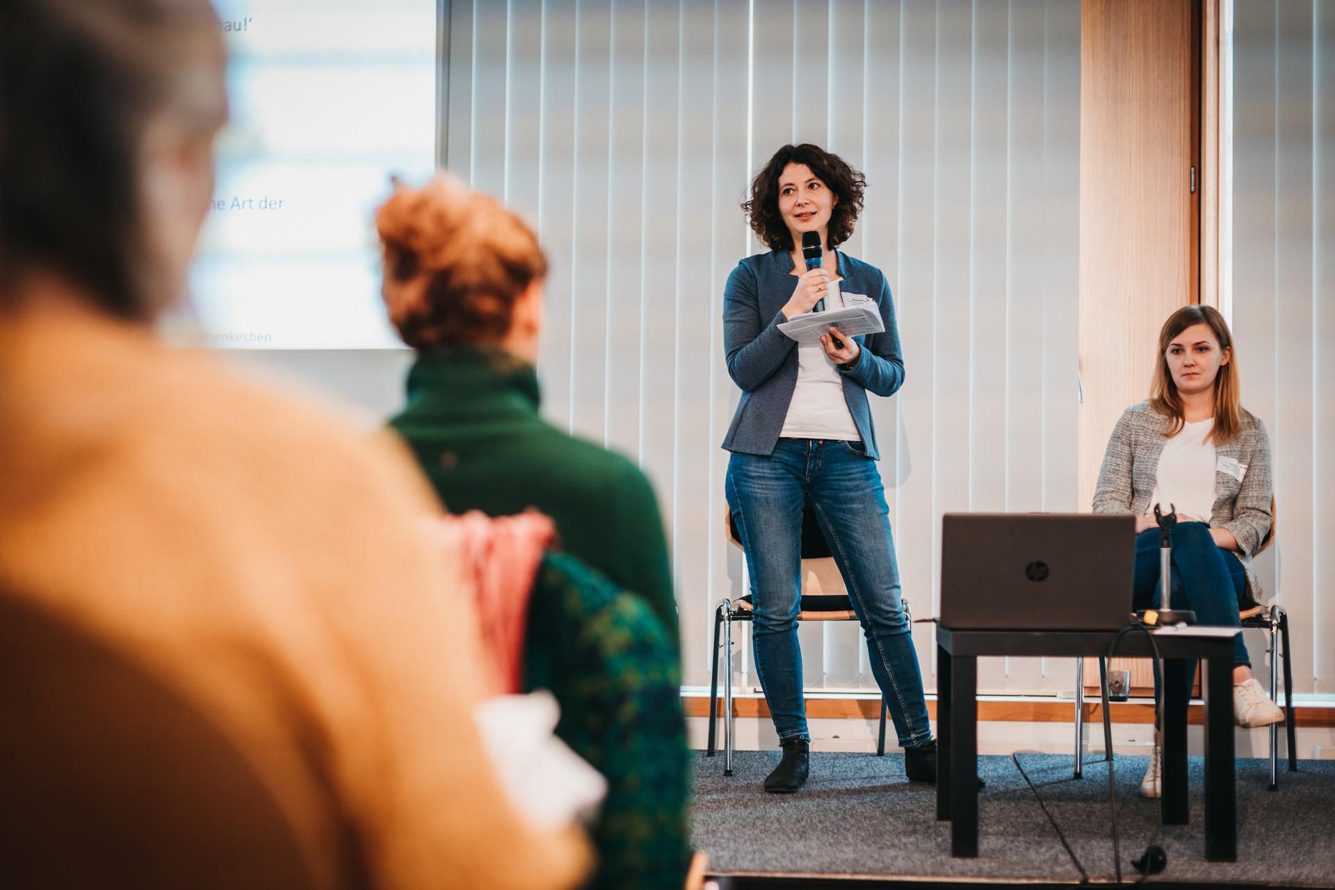 Merle Schmidt und Christina Baum auf einer Bühne. Merle Schmidt steht und spricht in ein Mikrophon, Christina Baum sitzt neben ihr. Im Vordergrund sind Personen aus dem Publikum von hinten zu sehen.