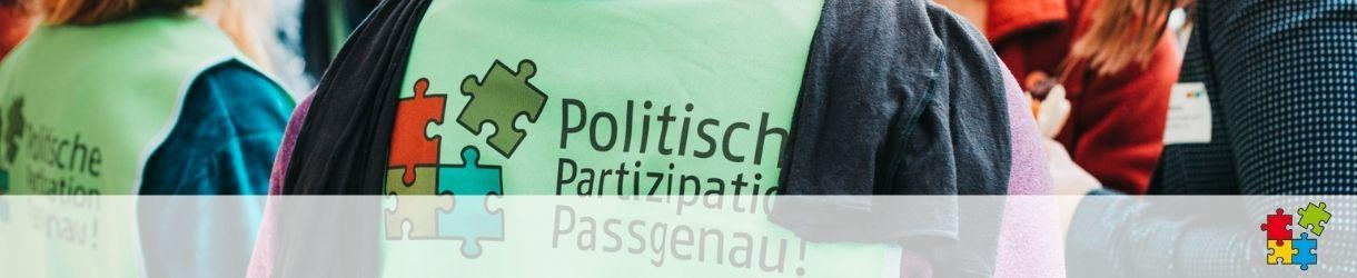 """Rückenansicht von zwei Personen. Sie tragen grüne Westen auf denen das Projektlogo zu sehen ist: Das Logo besteht aus vier bunten Puzzleteilen in gelb, grün, blau und rot sowie dem Projektnamen """"Politische Partizipation Passgenau!"""""""