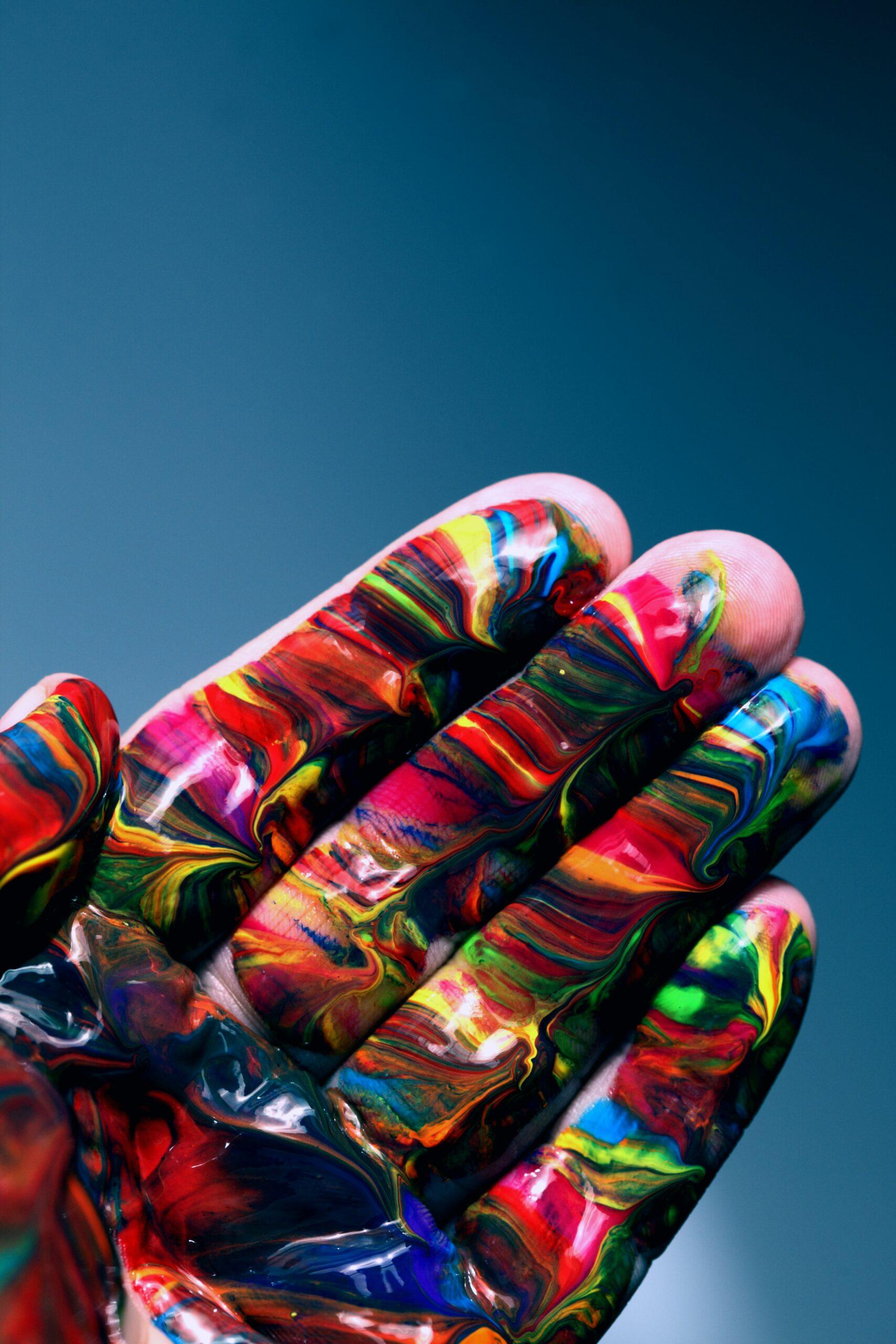Eine Handinnenfläche. Sie ist komplett mit flüssiger Farbe in vielen verschiedenen Farbtönen bedeckt.