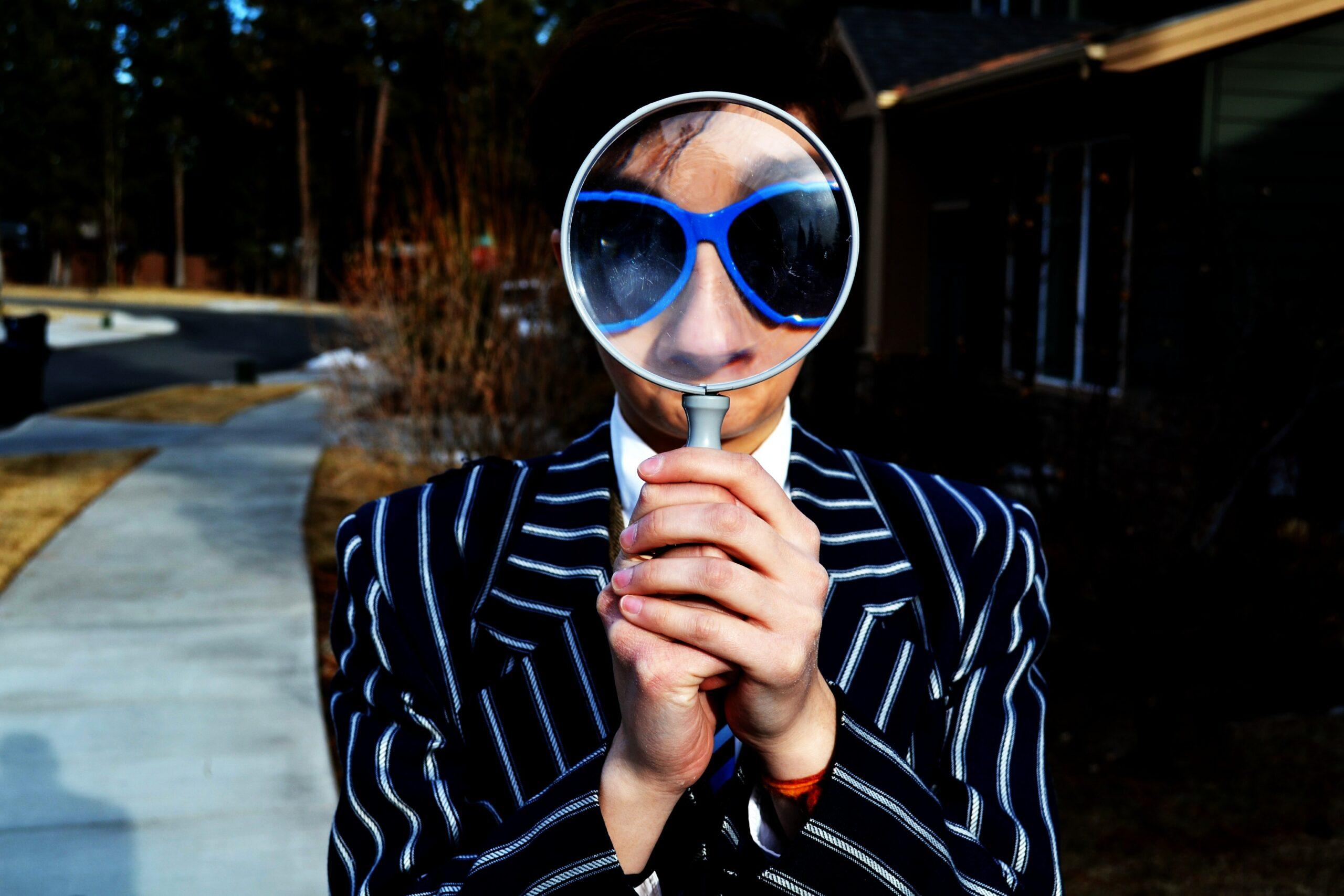 Ein Mann in einem gestreiften Jacket und einer großen blauen, auffälligen Sonnenbrillde hält eine große Lupe vor sein Gesicht. Seine Augen und seine Nase sind stark vergrößert. Es sieht etwas skurril bis witzig aus.